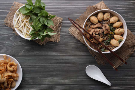 Asian noodles with pork, pork balls, pork crackling and vegetables on dark background. Close up Thai boat noodle culture style top view and flat lay with copy space for your advertising content.