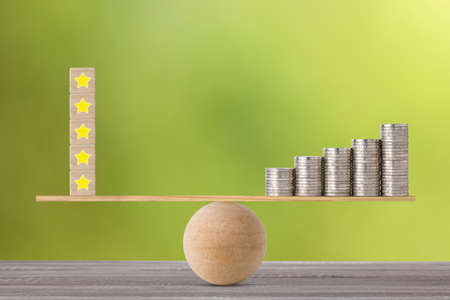 Excellent business five star rating experience on wooden block with stacking coin on seesaw balancing, meaning business gain money after customer satisfaction Stok Fotoğraf