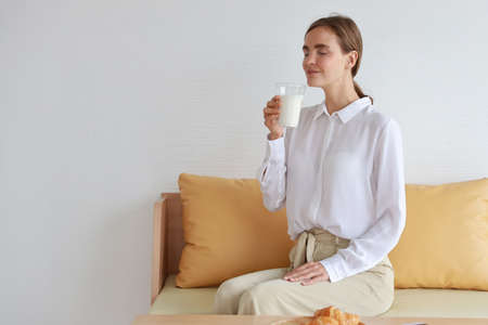 Young attractive caucasian woman wearing white casual clothes sitting in living room. Cute girl drinking a glass of milk with  croissants for breakfast while using mobile phone on table. Stok Fotoğraf