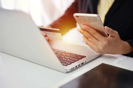 Woman hands in black suit sitting and holding credit card and using laptop computer on table for online payment or shopping online. Business woman using mobile phone while working. E-Banking concept