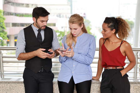 half length shot of happy smiling caucasian young businessman and businesswoman in formal wear, they arguing and discussing startup project with smart phone while walking during lunch break with urban view background