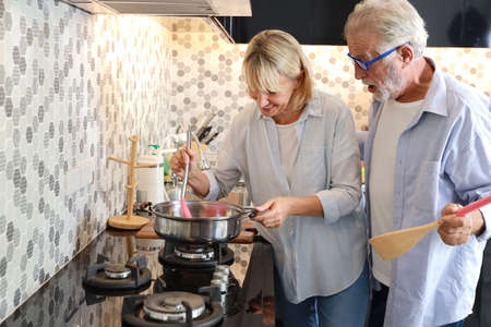 caucasian elderly wife making food in the kitchen with her caucasian elderly husband during his retirement life on table in happy holiday Stok Fotoğraf
