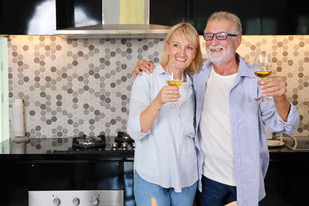 Couple senior caucasian husband and wife in casual dress standing, raising drink for cheers celebration in kitchen at house. Happy elderly man and woman holding glass of wine or cocktails with smiling