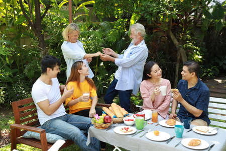 Happy multiethnic family standing and sitting at a breakfast table in backyard outdoor on sunny day with smiling face. Happy caucasian and asian family sitting and having conversation with good time outdoor.