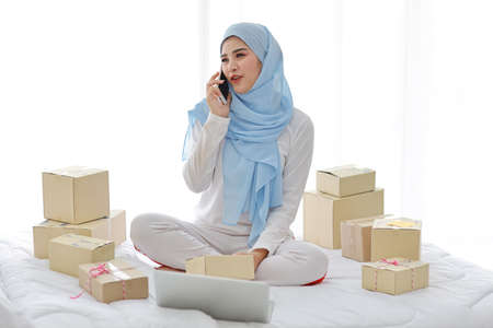 Active smiling asian muslim woman in sleepwear sitting on bed using mobile phone and computer. Startup small business SME freelance girl working with online package box delivery, E-commerce concept.