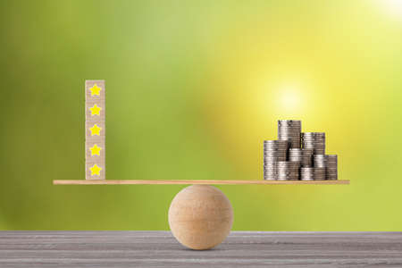 Excellent business five star rating experience on wooden block with money stacking coin on seesaw balancing, meaning business gain money after customer satisfaction