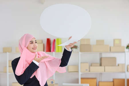 Active asian muslim woman in blue suit standing and holding white speech bubble with online package box delivery background. Startup small business SME freelance girl work at home with happy face. Stok Fotoğraf