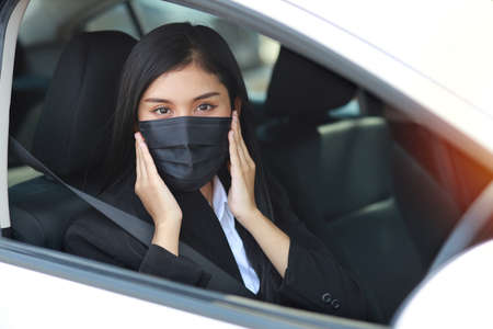 Young asian healthy woman in business black suit with protect mask for healthcare in automobile and driving car. New normal and social distancing concept