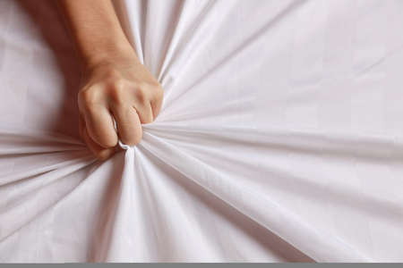 Close up young sexy woman hands pulling white sheets in ecstasy in hotel. Cute girl doing sign orgasm on white bed (sex and erotic concept for advertisement)