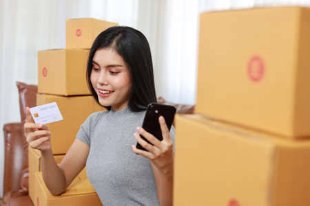 Young asian smart and active business woman in casual dress holding credit card and working from home with smartphone and online purchase shopping order box packaging (new normal concept)
