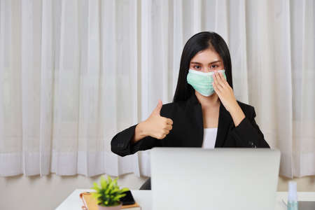 Young asian woman in black suit waring protect mask for healthcare and showing thumb up and sitting in office and working on computer laptop and smartphone. New normal and social distancing concept