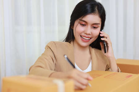 Young asian smart and happy business woman in casual dress working from home with laptop computer and smartphone with online purchase shopping order and box packaging on table (new normal concept) Stockfoto
