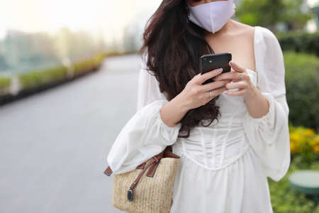 Young asian business woman hands in white casual dress with protect mask for healthcare, walking in public outdoor and working on smartphone. New normal and social distancing concept Stockfoto
