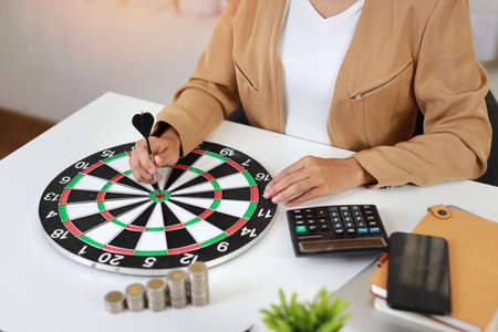 Smart and active asian businesswoman hands putting dart to target dartboard with saving growth on stacking coin on table, meaning of earning money or investment or tax for business advertising concept Stockfoto