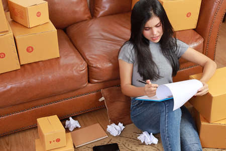 Young depress asian business woman in casual dress got headache from business failure from covid 19 with crumpled paper and online purchase shopping order box packaging (new normal concept)