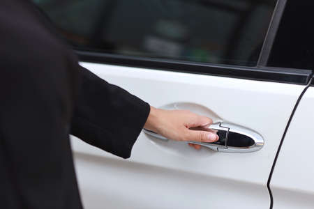 Close up female hand opening car or automobile door