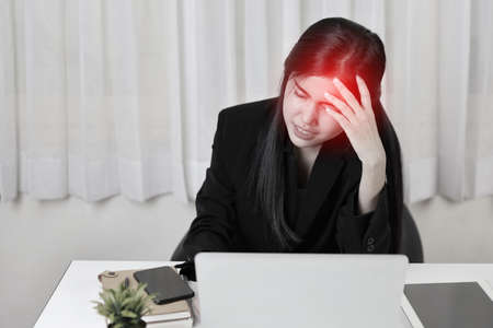 Young asian stressed businesswoman having problem or feeling pain touch temples suffer headache or migraine after working on computer for too long time. Office syndrome concept Stockfoto