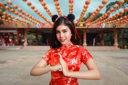 Beautiful young Asian woman in red Chinese dress traditional cheongsam qipao with gesture of congratulation and happy smiling face, she standing in front of ancient temple (Chinese new year concept)