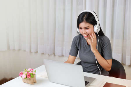 Young smart and active asian female student sitting at table with headset, using computer and taking note for studying online with happy smiling face (new normal concept)