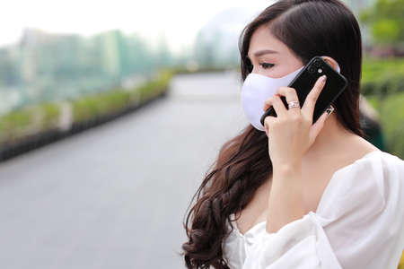 Young asian business woman in white casual dress with protect mask for healthcare, walking in public outdoor and working on smartphone. New normal and social distancing concept