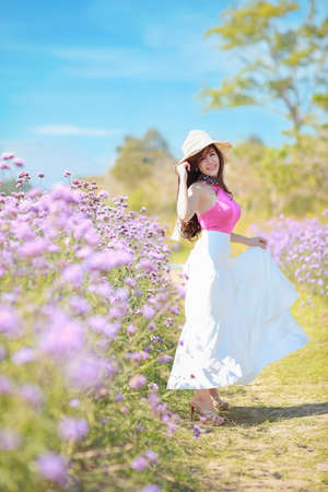 Asian beautiful woman, long hair in cute dress on Verbena filed in winter with blue sky. Beautiful cute girl portrait enjoying flowers in flowers farm background. Travel in nature outdoor concept
