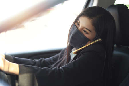Young asian healthy woman in business black suit with protect mask for healthcare in automobile and using smartphone and driving car. New normal and social distancing concept