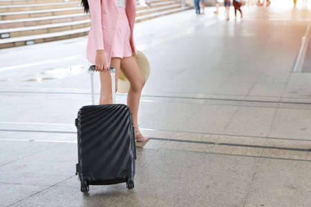 Traveler suitcase, Young asian business woman or traveler in pink casual dress carrying a black suitcase walking in a travel location on holidays trip Stockfoto