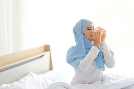 Beautiful and healthy asian muslim woman sitting on bed and drinking coffee or tea after getting up in the morning at sunrise in bedroom with happy and smiling face. Stockfoto