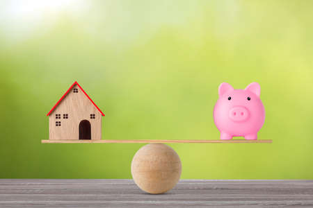 Model house on wooden seesaw balancing with piggy bank on green background. Property investment and home mortgage financial real estate advertising concept