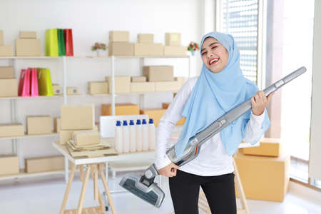 Happy young beautiful asian muslim housewife woman cleaning and playing vacuum cleaning like guitar with SME and E-commerce Package box background. Cleaning girl in black leggings vacuuming her room.