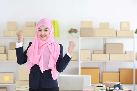 Religious asian muslim woman in blue suit and pink shaft standing and looking at camera with exciting emotion. Business woman stand with package SME box delivery background. Work at home concept
