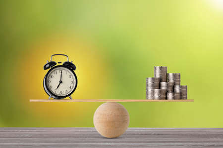 Alarm clock on seesaw balancing with stacking coins money on wooden table, meaning of business investment and saving growth with time for advertising concept.