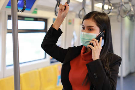 New normal   epidemic, young business asian woman wearing mask protection for prevent virus  infection from people in train, using smartphone communication in train