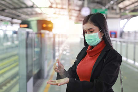 New normal   epidemic, young smart business asian woman wearing mask protection for prevent virus   infection from people in train, using alcohol spray hand sanitiser