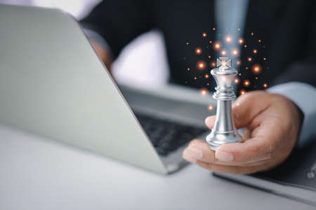 Businessman hands in black suite sitting and holding chess king on vintage table with computer on table meaning of planning and strategy. Decision and achievement goal concept.