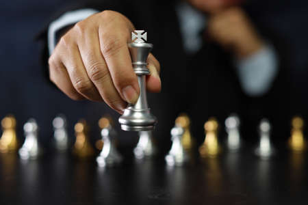 Businessman hands in black suite sitting and pointing chess king on vintage table meaning of planning and strategy. Decision and achievement goal concept.