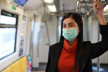 New normal  epidemic, young smart business asian woman wearing mask protection for prevent virus   infection from people in train or bad air pollution PM2.5 dusk Stockfoto
