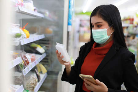 Young smart business asian woman wearing face mask looking and choosing grocery to buy from shelf in supermarket department store or shopping mall,