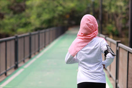Rear view portrait sporty young asian muslim woman in sportswear jogging outdoor for marathon training. Jogger girl exercising along concrete path outdoor with green tree background. Sport concept