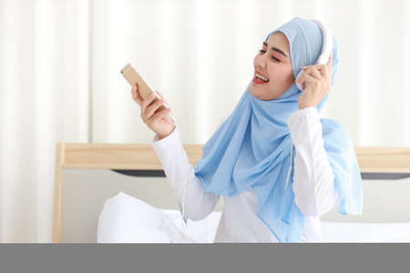 Portrait of beautiful asian muslim female in sleepwear watching online story on mobile phone, sit on bed and connected with wireless internet. Young cute girl with hijab listen music from smartphone