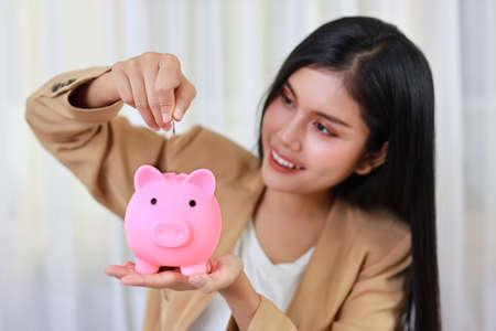 Smart and active asian businesswoman putting coin into piggy bank (focus on hand), meaning of earning money or investment or tax for business advertising concept