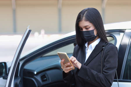 Young asian healthy woman in business black suit with protect mask for healthcare get off automobile and using smartphone. New normal and social distancing concept Stockfoto