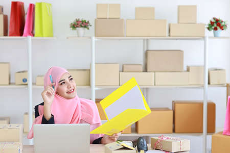 Active asian muslim woman wearing suit sitting and holding folder with computer and online package box delivery. Startup small business freelance working girl thinking of something with copy space.