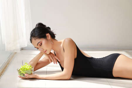 close up beautiful healthy and sporty asian young woman holding salad bowl and eat after training ballet dancing while lying down Stockfoto