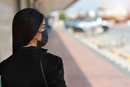Rear view young asian business woman in business black suit with protect mask for healthcare walking on street public outdoor and looking way. New normal and social distancing concept Stockfoto