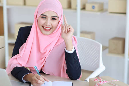 Active asian muslim woman in blue suit sitting and working with computer and online package box delivery. Startup small business freelance working girl look at camera with smiling Stockfoto