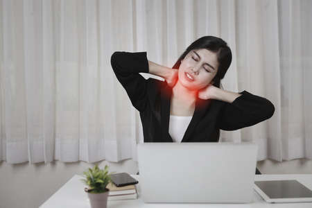 Young asian stressed businesswoman feeling pain or having problem with part of body neck or arm shoulder after working on computer for too long time. Office syndrome concept Stockfoto