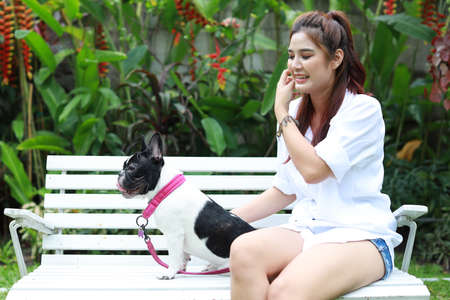 beautiful young asian woman wearing white shirt sitting on white bench and playing with cute dog with happy laughing face Stockfoto