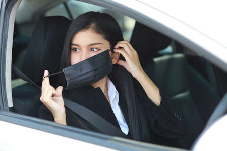 Young asian healthy woman in business black suit wearing protect mask for healthcare in automobile and driving car. New normal and social distancing concept
