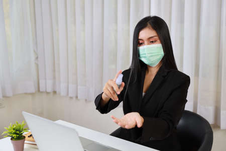 Young asian woman in suit waring protect mask and use alcohol spray hands sanitiser for healthcare and sitting in office working on computer and smartphone. New normal and social distancing concept Stockfoto